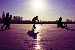 Ice skating at sunset in the Netherlands. Ice skating on a frozen lake at sunset in the Netherlands Stock Photos