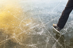 The ice skating tracks, a man stands beside her. Stock Image