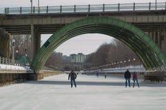 Ice skating under the bridge on the frozen Rideau Canal Ottawa W Stock Photos