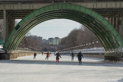 Ice skating under the bridge on the frozen Rideau Canal Ottawa W Stock Photo