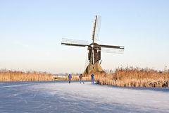 Ice skating in winter in the Netherlands. Typically dutch: ice skating on a frozen lake at Kinderdijk with view on a windmill on a cold winterday in the Royalty Free Stock Image