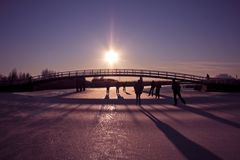 Ice skating in winter in the Netherlands. Typically dutch: ice skating on a frozen lake on a cold winterday in the Netherlands at sunset Royalty Free Stock Images