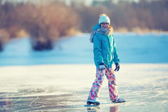 Ice skating. Young girl is skating on a natural frozen lake Royalty Free Stock Images