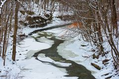 Ice and snow on the Chagrin River. The Chagrin River cuts a narrow channel through ice and snow below the falls in Chagrin Falls, Ohio royalty free stock image