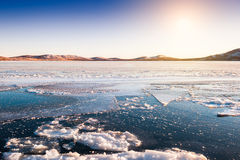Ice and snow on the lake at sunset Royalty Free Stock Photos