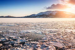 Ice and snow on the lake at sunset Royalty Free Stock Images