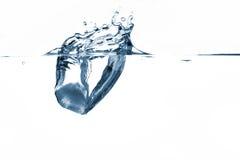 Ice splash. Ice cube splashing in water stock photo