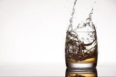 Ice splash into whiskey or brandy Stock Photo