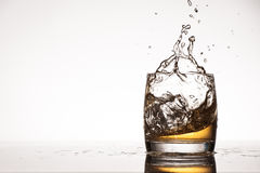 Ice splash into whiskey or brandy Royalty Free Stock Image