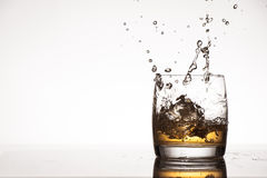 Ice splash into whiskey or brandy Stock Photography