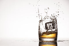 Ice splash into whiskey or brandy Stock Images