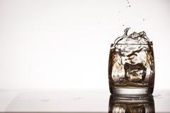 Ice splash into whiskey or brandy Royalty Free Stock Photo