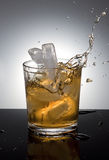 Ice splashes into drink. Stock Photography