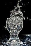 Ice splashing into a glass on white. On black background Royalty Free Stock Image