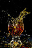 Ice splashing into a glass on yellow. In black background Stock Photography
