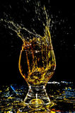 Ice splashing into a glass on yellow 1. Ice splashing into a glass on yellow in black background 1 Stock Image