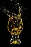 Ice splashing into a glass on yellow 1. Ice splashing into a glass on yellow in black background 1 Stock Photography