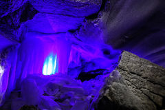 Ice stalactites blue color in cave in stunning texture of rock, covered with frost stock photography
