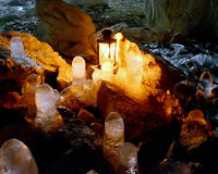 Ice stalactites in the cave. Ice stalactites in a cave with a decorative candle on an old lamp Royalty Free Stock Image