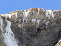 Ice stalactites and frozen waterfall on a rock face Stock Photography