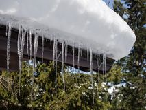 Ice stalactites hanging from the roof of a wooden house in the mountains. During winter royalty free stock images