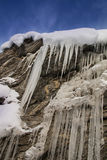 Ice stalactites under blue sky. With some clouds royalty free stock image