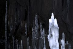 Ice stalagmites in the cave. Focus on the front, the biggest icicle, the rest are blurred and in the half-darkness stock photography