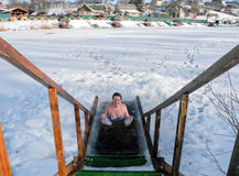 Ice swimming in the winter ice-hole after a sauna. Women plunge into the winter ice-hole in lake after a sauna Stock Photos