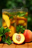 Ice tea. Glass of fruity ice tea with peaches and mint Stock Image