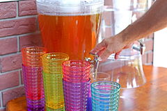 Ice tea dispenser with festive glasses. A man is pouring himself a glass of ice tea from a large dispenser with festive tall glass resting on the side Stock Image