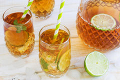 Ice tea in a glass with a slice of lime. White wooden plank back. Iced tea in a glass with a slice of lime. White wooden plank background Stock Photo