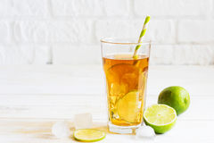 Ice tea in a glass with a slice of lime. White wooden plank back. Iced tea in a glass with a slice of lime. White wooden plank background Stock Photography
