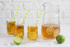 Ice tea in a glass with a slice of lime. White wooden plank back. Iced tea in a glass with a slice of lime. White wooden plank background Royalty Free Stock Images