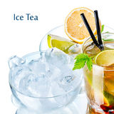 Ice tea. Iced tea in the glass decorated with leaves near a transparent saucer with tea ingredients Stock Images
