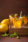 Ice tea with lemon and mint on dark rustic background Royalty Free Stock Photos