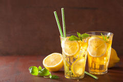 Ice tea with lemon and mint on dark rustic background Stock Images