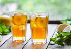 Ice tea with lemon slices and mint on wooden table with a view to the terrace. Close up summer beverage. Ice tea with lemon slices on wooden table with a view to stock photography