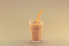Ice tea with milk in glass cup on grain paper background Stock Photo