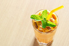 Ice tea with milk and mint in glass on wooden background Stock Image