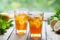 Ice tea summer refreshing cocktail drink on wooden table with a view to the terrace and trees. Close up summer beverage Stock Photography