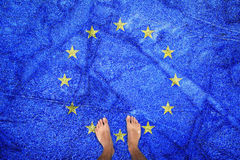 Ice textured eu flag with barefoot man Stock Image