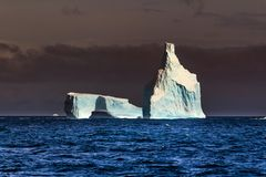 Ice tip of the iceberg, the age-old ice, the sun shines through. Close-up. Antarctica stock images