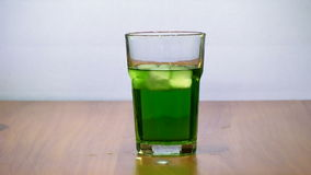 Ice turns in a funnel, in a glass with tarragon estragon slowmotion stock video footage