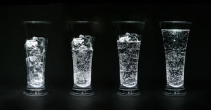 Ice-water. Four glasses filled up with ice and water royalty free stock photos