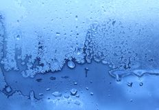 Ice and water drops texture. Blue ice and water drops on winter glass Royalty Free Stock Image