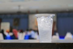 Ice water in glass-plastic in seminar conference room background. select focus with shallow depth of field royalty free stock images