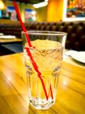 Ice water with red suction tube. The glass is placed on the wood Royalty Free Stock Photo