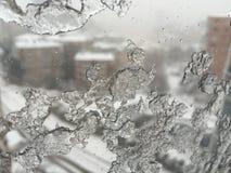 Ice on window against street under snow Stock Photos