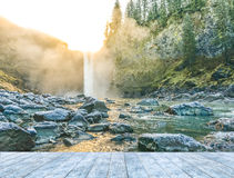 Ice wooden table with background of scenic view of water fall when sunset. Royalty Free Stock Images
