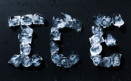 Ice written with ice cubes on dark background Stock Images